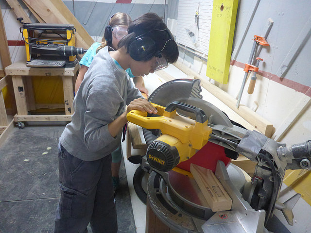 Dylan uses the chop saw to cut a miter.