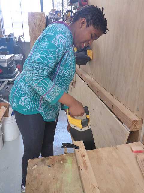 Katia uses the hand saw to work on her personal project.