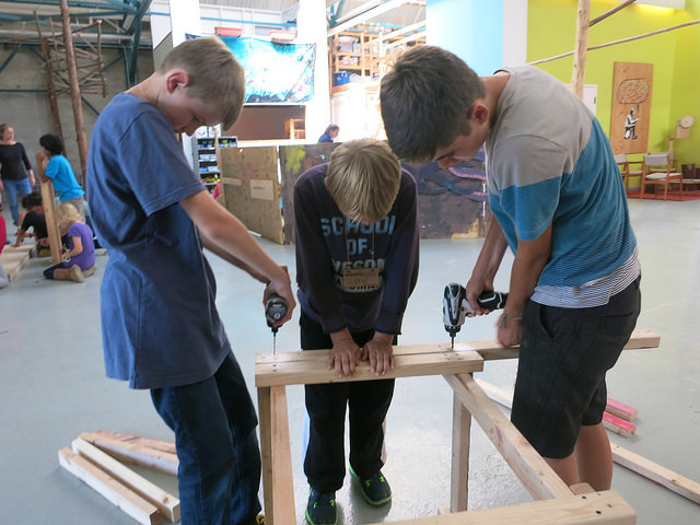 Owen, Ethan, and Leo add supports to the bottom of the Balloon Rocket tower.