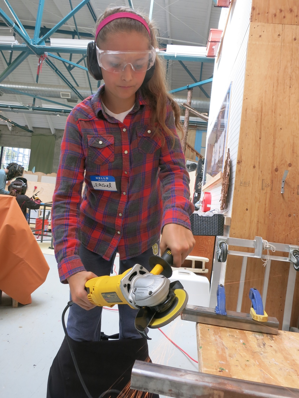 Rachel grinds a bevel onto a piece before welding.