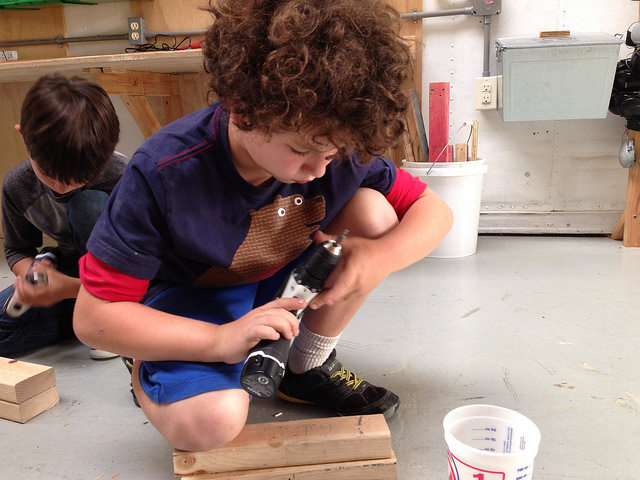 Gabriel makes good use of his knee to clamp his wood while preparing his drill to drive his first screw.