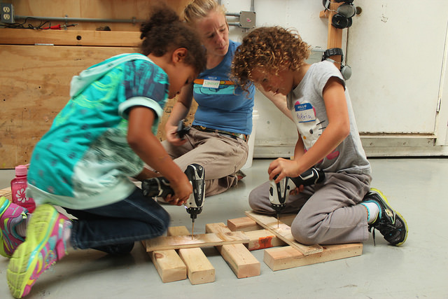 Cecilia moves her keen to steady the wood while Portia practices posture and how to use her body's weight to drill a hole.