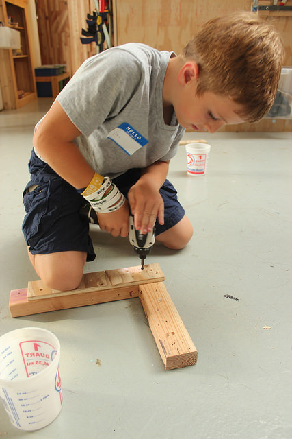 Liam configures his single piece of strapping to attached both of the pieces he cut on the chop saw.