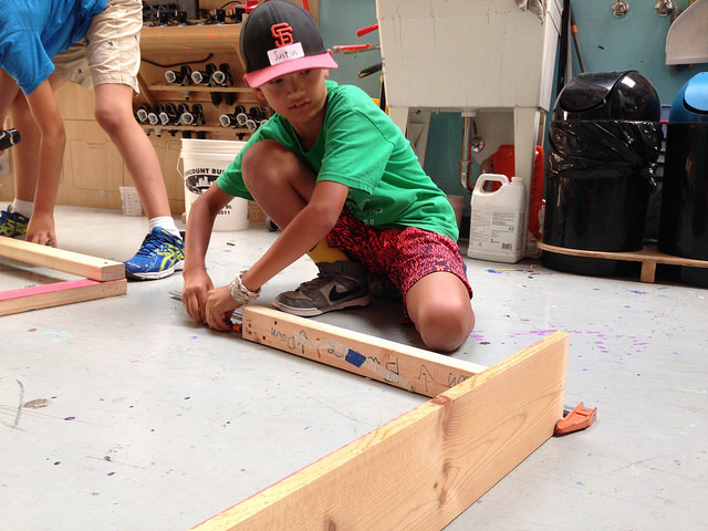 Justin positions a clamp along one end of a three legged stool