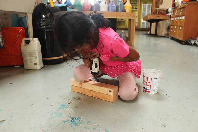 "driving a 2"" drill bit through 3 inches of wood can be challenging to a 5 year old. Anaya tries to leverage her body weight to push her drill into the wood"