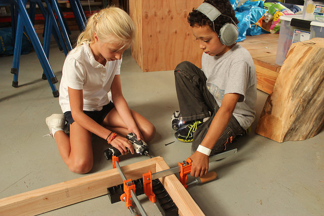 Cami and Lukas pair up to attach parts of the floor frame. Having one person drill and one drive screws proves to be much more efficient then working alone and switching out drill bits.
