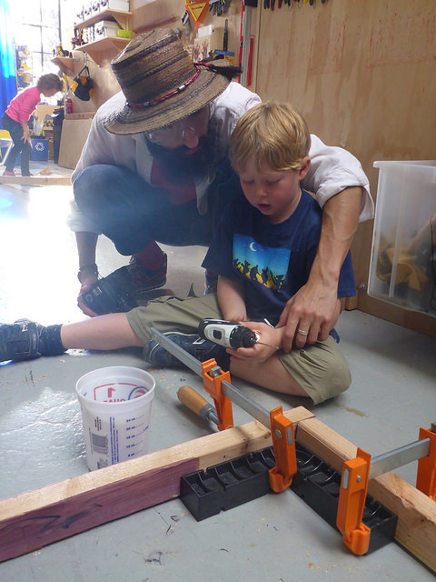 Nathan reviews how to use reverse on the drill with Owen who is working on a section of framing for the sub.