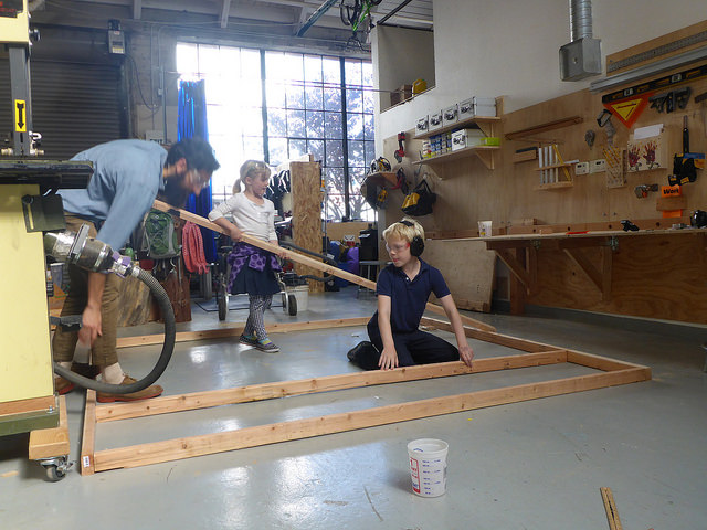 Ida and Lincoln help set the supports in place for the floating room floor.