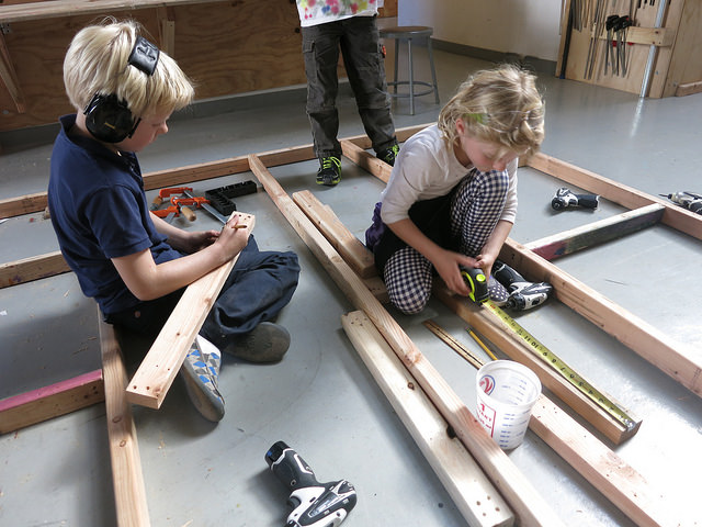 Lincoln and Ida diligently measure and mark more cross supports for the floor team to attach.