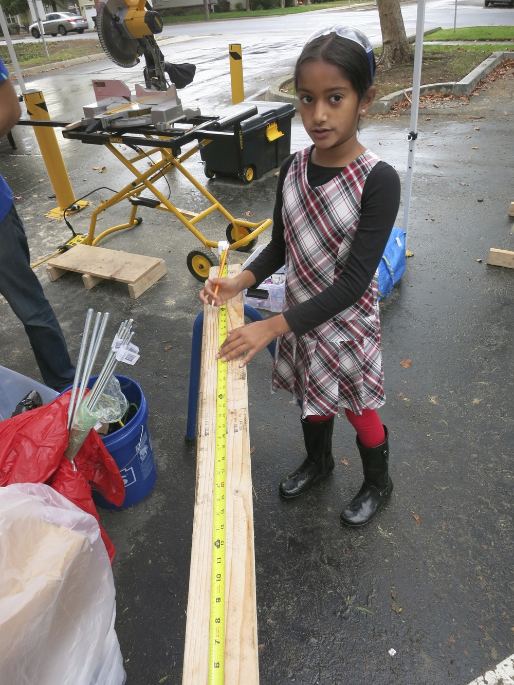 Undeterred by the rain, Riya marks a cut for the bleachers.