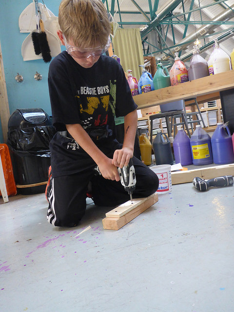 Ruaricomplete's his basic shop training by practicing with a drill in preparation to assemble hisappetizerproject