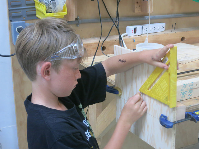 Ruari learns how to mark using a rafter square to ensure his screws make in into the wood.