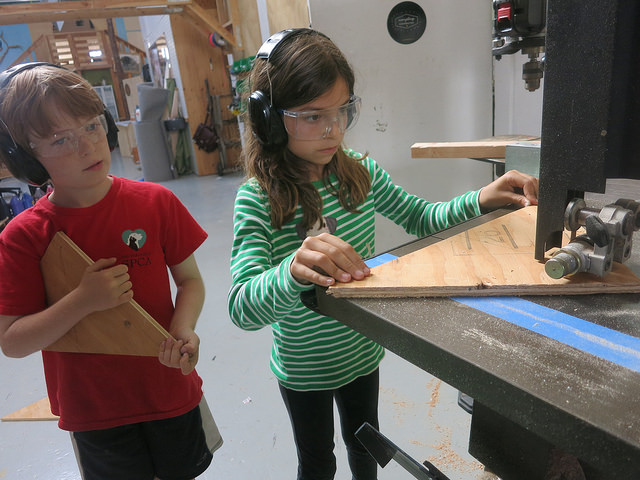 Emilia and Zach work on gutting out gussets on the bandsaw to help stabilize the wobble on the frames