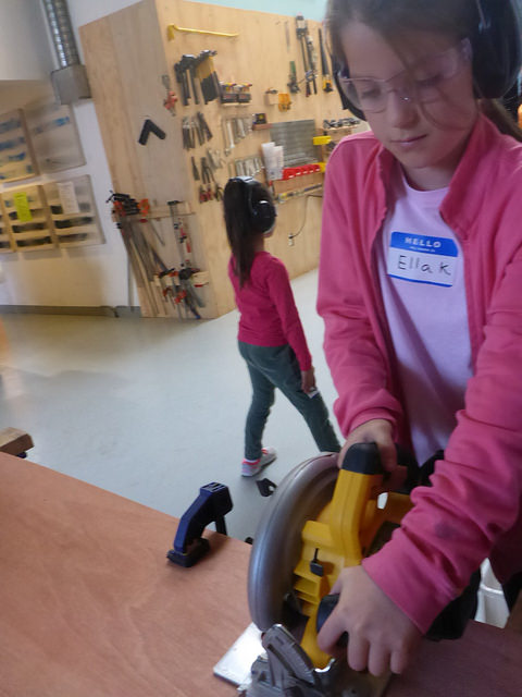 Ella takes a turn using the skilsaw to cut a straight line.