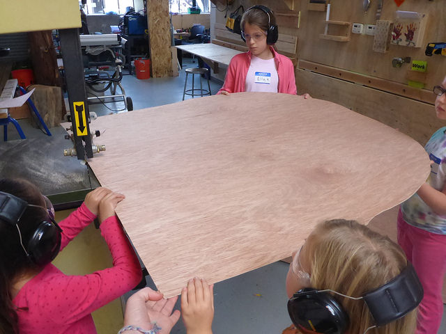 Francesca curves her corner through the bandsaw while the rest of the team supports the weight.
