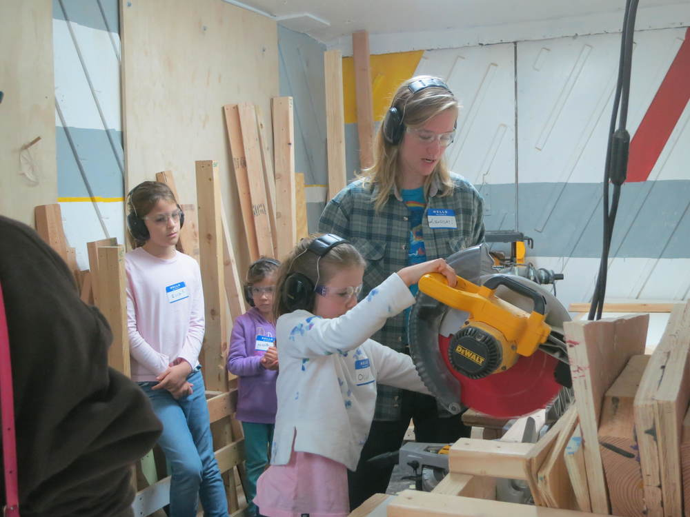 Olivia practices using the chop saw safely.