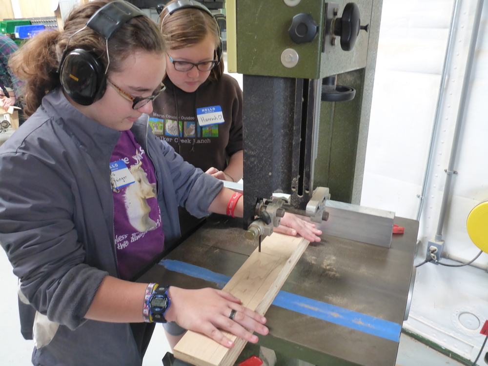 Sophia cuts the parts on the bandsaw!