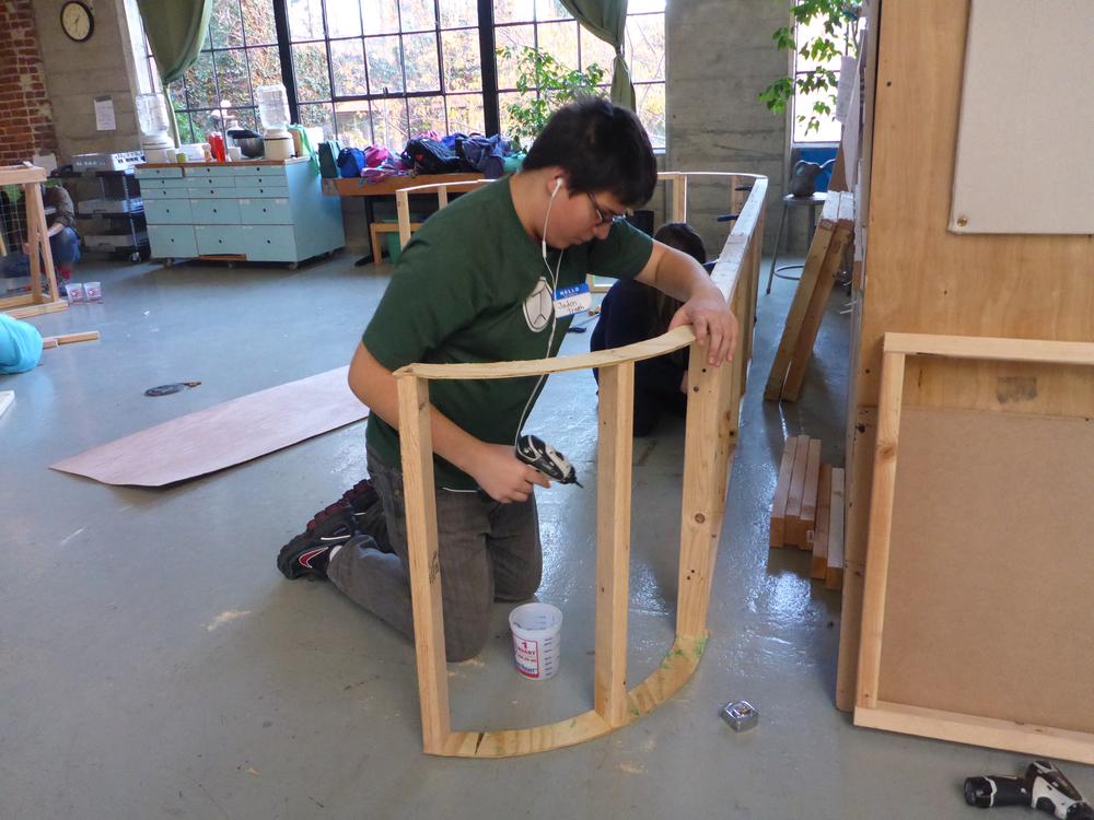 Jadon installs the framing for a curved rink corner.
