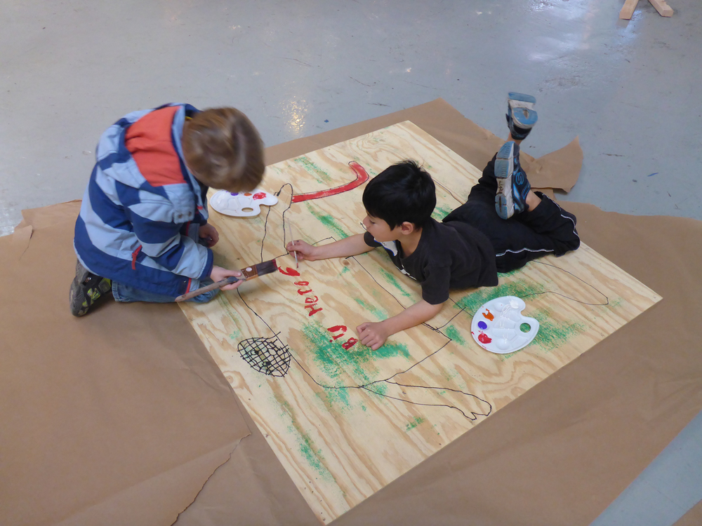 Lev and Zachary paint a goalie.