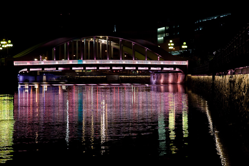 It is Chinese New Year here in Singapore, and I went out with my DSLR before sunrise to see what night lights might be of interest. This morning, I decided to turn left after crossing the Cavanagh Bridge, and walked towards Boat Quay and Elgin Bridge. As the bridge came into full view, I could see that the lights were creating striking pink and red-toned reflections in the Singapore River. I walked down the stairs at a tour boat boarding area and set up my tripod to make a few photos. Below is my favorite of the lot.