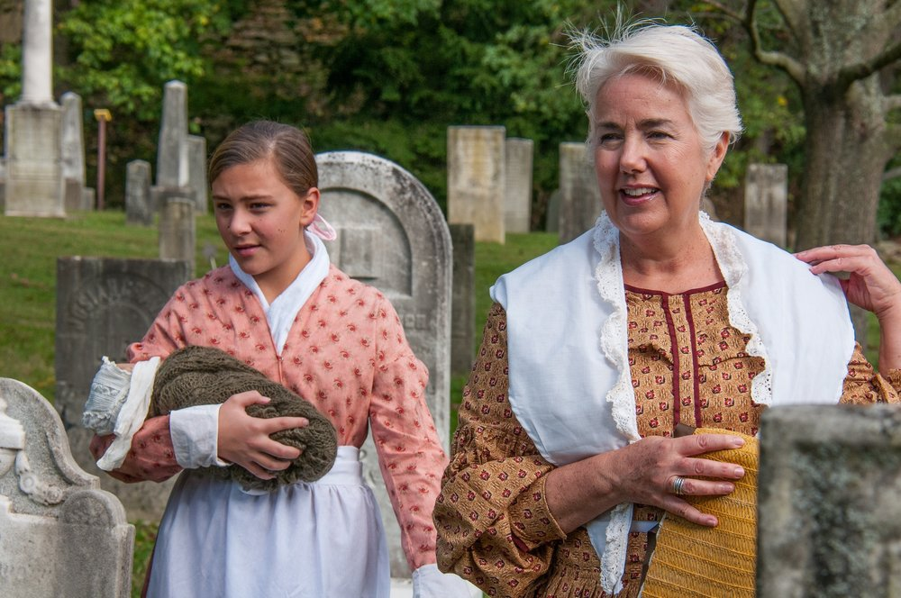 Sally Leithauser as Mary Root (holding her infant sister, Dameris) and Deb Eddy as Mary Barret Root.
