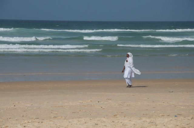 Even though the lines of the waves and horizon are very strong, the lady in white is the most dominant point in the image, and in the shape of a vertical line.