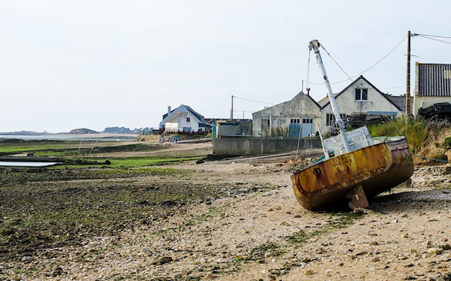 Fisherboat stranded on the shore. The boat will only be able to sail out when the water reaches its highest level.