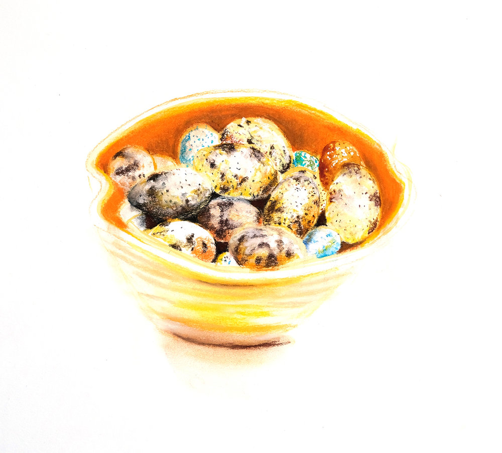 Quail eggs in yellow and orange bowl