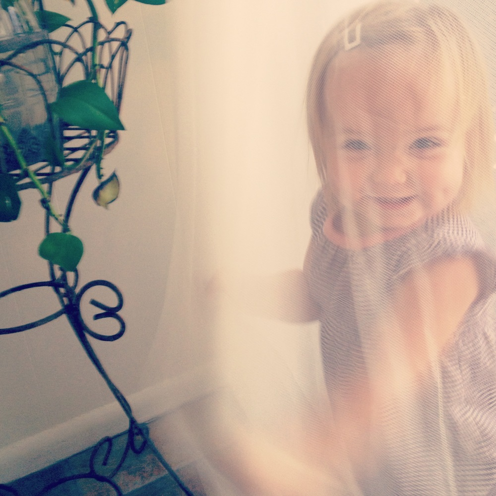 Twirling in the curtains.  Every little girl should.