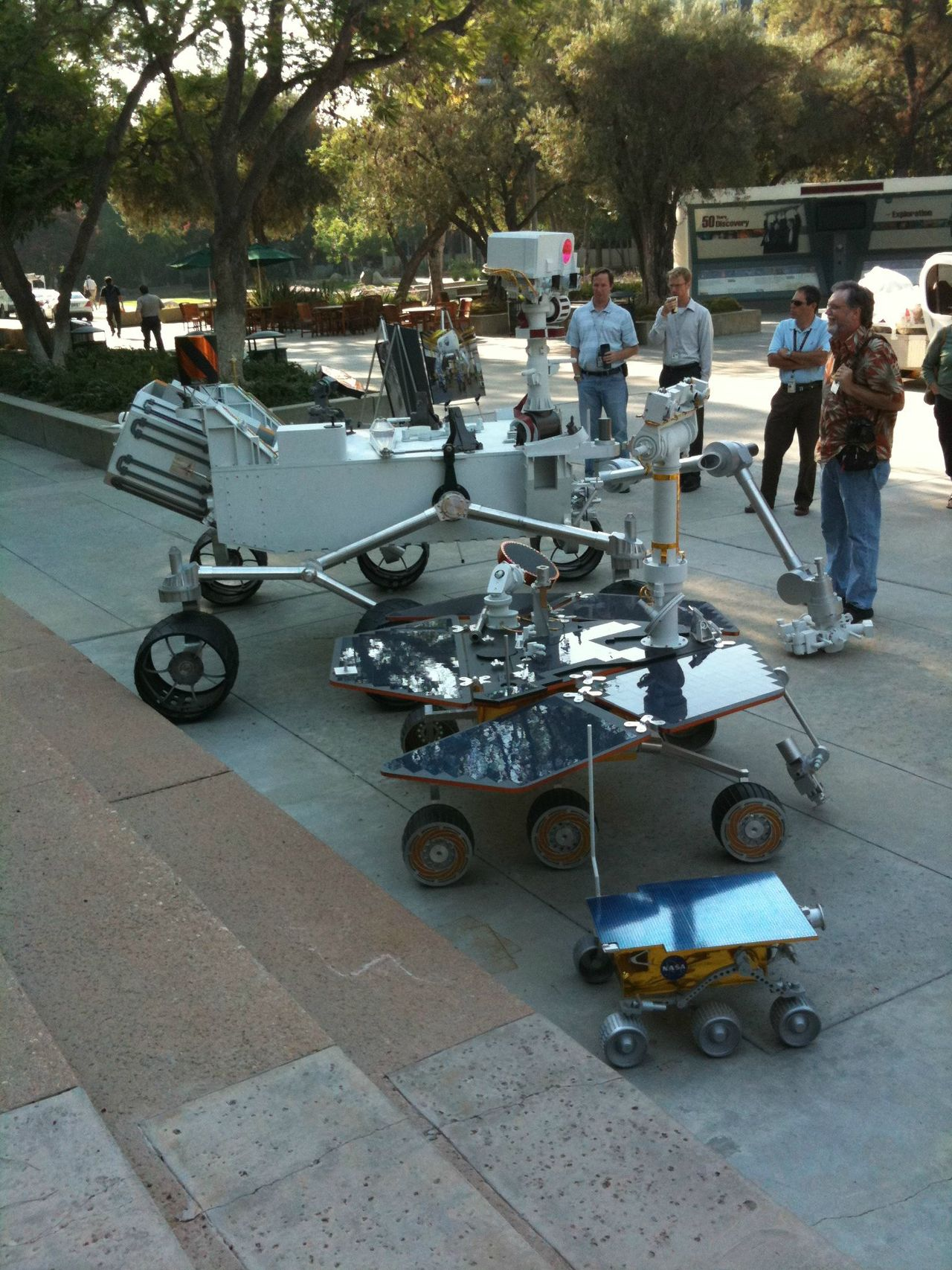 "spytap :     In honor of Curiosity's successful landing, I present ""Three Generations,"" courtesy of John Klose , JPL employee since 2002. It shows the Mars landers Spirit (foreground), Opportunity (middle), and Curiosity (background) taken in front of JPL building 180, aka the Directors building.     3xDope"