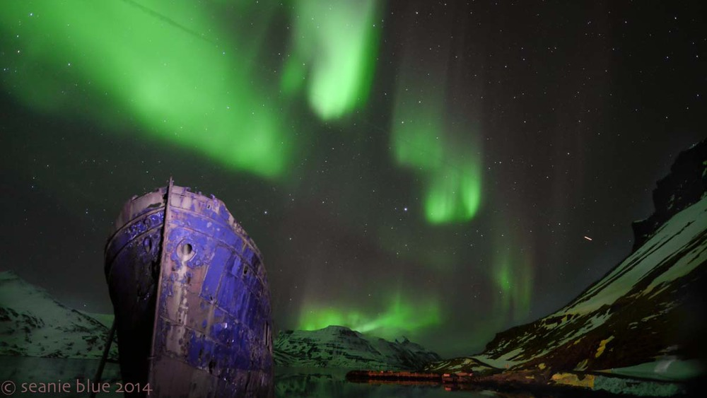 In Djupavik with the abandoned herring ship as an airplane flies in front of the Aurora.