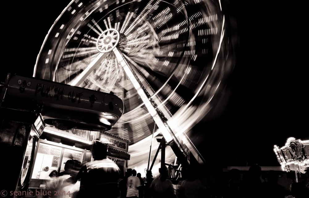 The ferris wheel is the action, blurred by a slower exposure, but the people in the foreground give the picture its life.