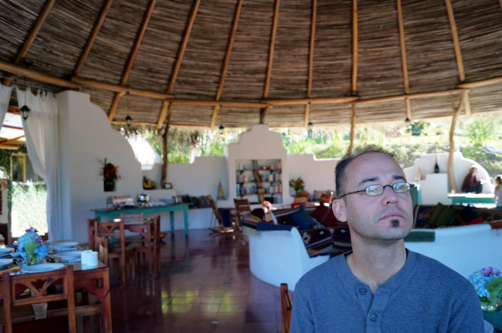My husband, Andy, sipping coffee one morning in the Maloka. To the left is one of the dining tables, then the table where food is served, then the library area, and finally the mandala coloring table. The white circular seating area directly behind him is the fire pit.