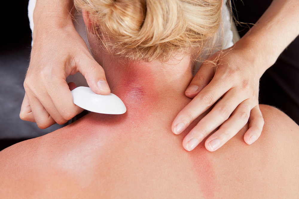 gua sha on the neck with a ceramic soup spoon