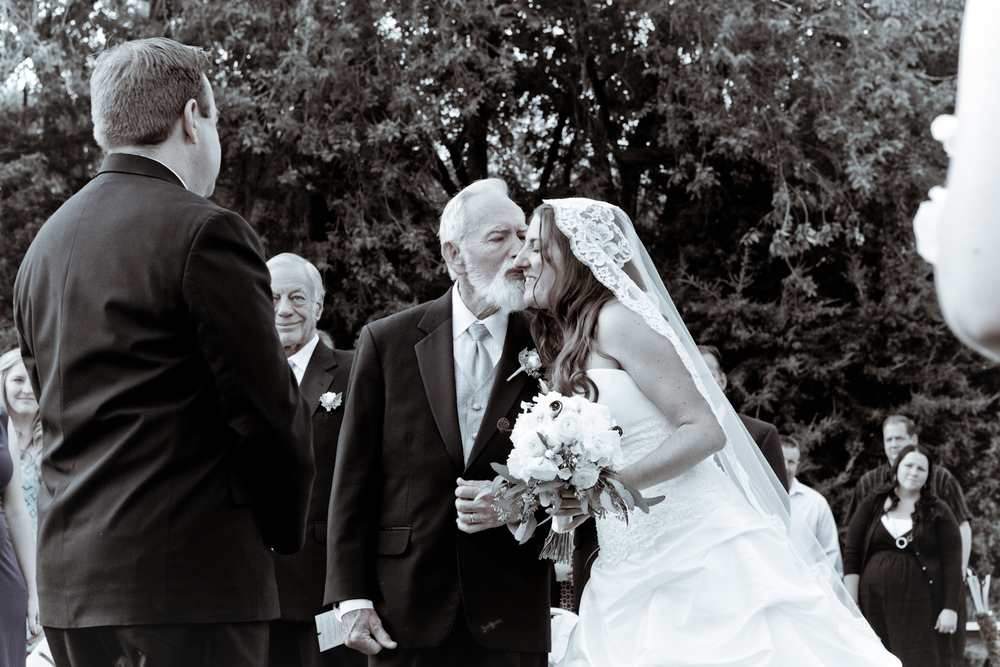 Loving father kisses his daughter on the cheek as he gives away the bride at outdoor wedding ceremony.
