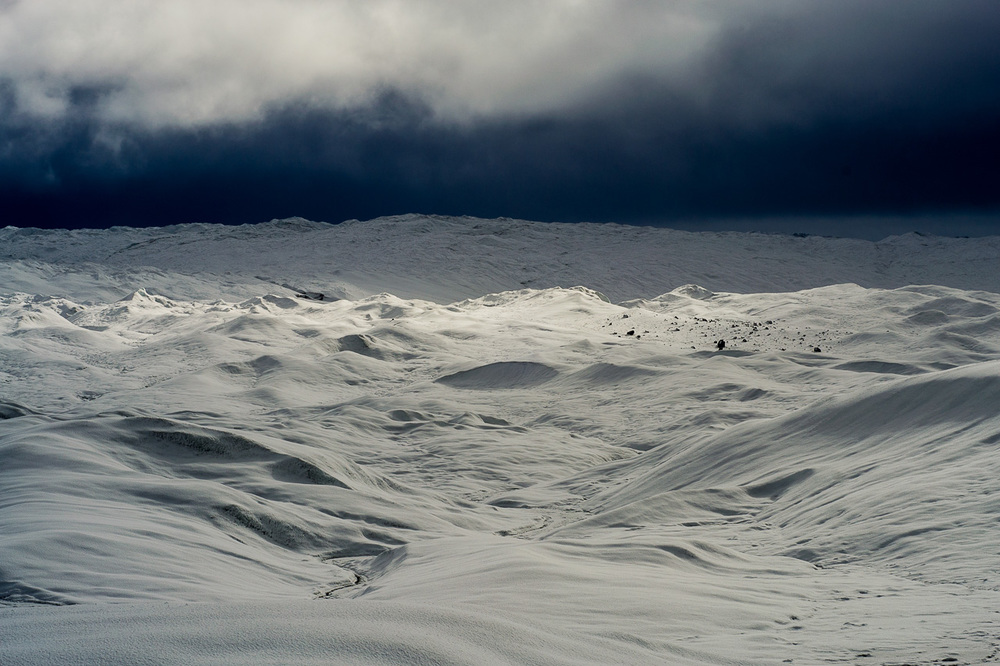Point 660, Grónsko, 1. listopadu 2012 Asi tak jako když se pořádně nasranej pes snaží utrhnout ze řetězu. Asi tak jako se snaží vosa dostat z flašky od piva. Anebo asi tak jako se důchodci snaží každý čtvrtek dostat k regálům se zlevněným zbožím v Lídlu. Prostě tak to Džordče a mě táhlo na ledovec. Stáli jsme pod tím krasavcem. Vlastně jsme ani nepotřebovali vědět jak se vyškrábat nahoru, neb jsme prostě začali levitovat a ledovec si nás nahoru přitáhl jako hodně silný magnet. Protože se pro přílišnou hlučnost smazal záznam našeho intercomu, uvádím zde doslovný přepis rozhovoru během první krátké návštěvy toho největšího nanuka jakej jsme kdy viděli. [Džorč]: Uuuuuaaaaaaeeeeeeeeaaaaaaaaaaaaaaaaa!!! To je fon!!! Jdeme nahoru pánové. [Já, již za horizontem mířícímu Džorčovi]: Že váháš! [Ondřej, který již nemá ke komu mluvit]: Je to rozumné? Nebudete to moc klouzat? Nemáme mačky pánové. [Džorč]: Sem tady!!! Kua, ještě kdyby bylo líp. [Ondřej]: Pěkný. Dá si někdo müsli tyčinku? [Já]: Ty voe jaký líp, vždyť je to tady úžasný, čum na ty mraky. [Džorč]: No právě, ty mraky. Není skoro nic vidět. [Ondřej]: No právě, není nic vidět. Asi přijde bouřka. Neměli bychom jít dolů? [Já]: Voe jaký dolů? Mě už vodtud nedostaneš! Nikdy! [Ondřej]: Jestli nás ta bouřka chytne tady, bude to prekérka. [Džorč]: Ondra má pravdu. Proto jdeme dál! Ještě kdyby tak vyšlo slunko na chvilu. [Ondřej]: Je tu chladno, že? [Já]: Uuuuuaaaaaaeeeeeeeeaaaaaaaaaaaaaaaaa!!! Slunko se dere, támhle vzadu, čumte na to! CWAK. CWAK. CWAK. CWAK. CWAK. Nádech. CWAK. CWAK. CWAK. CWAK. CWAK. Výdech. [Džorč]: Hlavně nelez do tý praskliny. To už bysme ani nevolali pomoc jo? [Ondřej]: Ještě tu mám oříšky. O několik minut později přišla sněhová bouře jako prase. Ondřej měl pravdu, jako úplně vždycky. Ale nám to bylo jedno.
