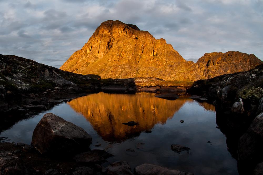 Poslední večerní paprsky osvěcují monumentální horu Nasaasaaq (784 m.n.m.), nedaleko přímořského města Sisimiut, které představuje se svými pět a půl tisíci obyvateli druhé největší grónské město.