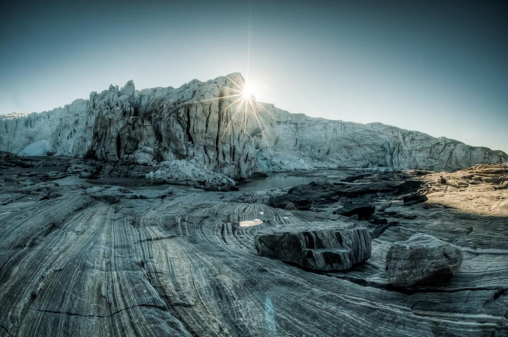 Východ slunce nad Russelovým ledovcem a řekou Akuliarusiarsuup Kuua. Přestože to není na první pohled zřejmé, toto místo je velmi nebezpečné. Díky pohybu ledovce a nestabilitě jeho čela mohou často velké kusy odtátého ledu padat i velmi daleko od vlastního ledovce.
