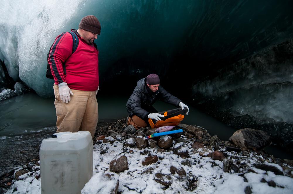 Mikrobiologové Markus Dieser a Erik Broemsen z Luissianské státní univerzity provádí odběry bakterií z potoku pramenícího pod ledovcem na Kótě 660. Nezbytnou součástí odběru vzorku tvoří měření chemických vlastností vody multiparametrickými sondami.