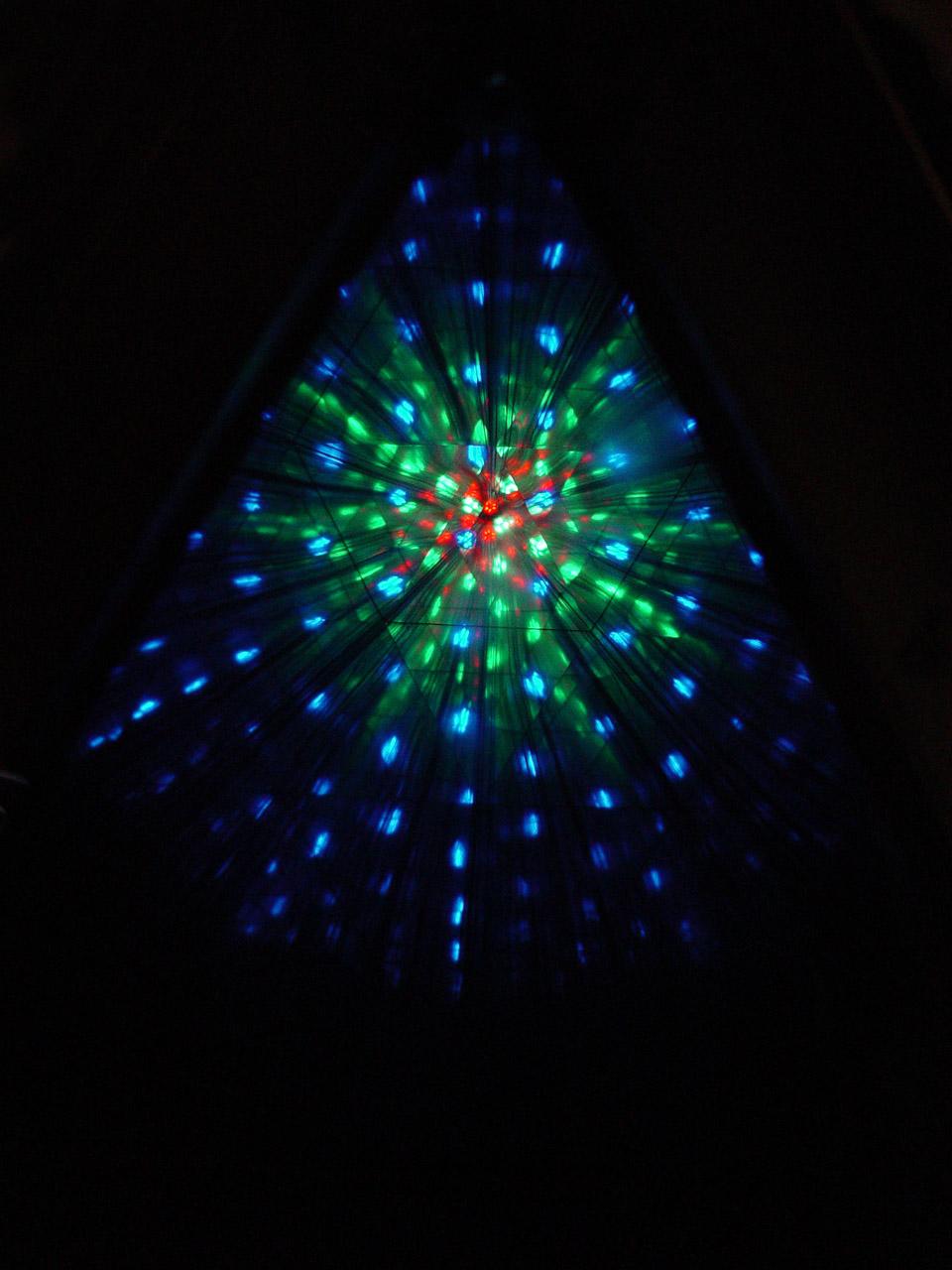 """Světelný tunel. Odraz světelného zdroje ve světelném tunelu tvořeném zrcadly. Zdrojem byly LED diody, které se daly v tunelu přemísťovat a vznikaly tak rozmanité obrazce. Snímek byl pořízen na interaktivní výstavě Labyrint světla (Ekotechnické muzeum v Praze, květen """" červenec 2009), exponát Světelný hranol s jezdci, autor O. Smeykal. Foto P. Bohatý"""