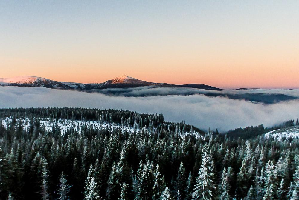 2. ledna 2014 Nandat na baťoh lyže a vrtulník, nastoupat příkrým svahem přes 600 metrů na Černou horu, jezdit, lítat, fotit. Po západu slunce zjistit, že se zvedá inverze a Sněžka bliká do krajiny mraků jako maják do rozbouřeného moře. Vzlétnout s poloprázdnou poslední baterií, rychlá fotka, rychle dolů. Zmrzlými prsty složit vrtulník a po tmě hurá zpět do mraků. Vlastně stačilo celkem málo, a momentka zimních Krkonoš je na světě :-)