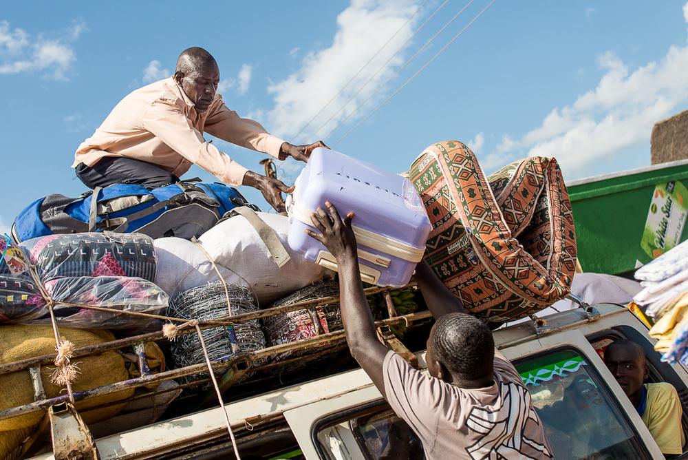"""Vrtulník (v bledě modrém kufru) se stěhuje na střechu autobusu, kterému místní neřeknou jinak, než """"matatu""""."""