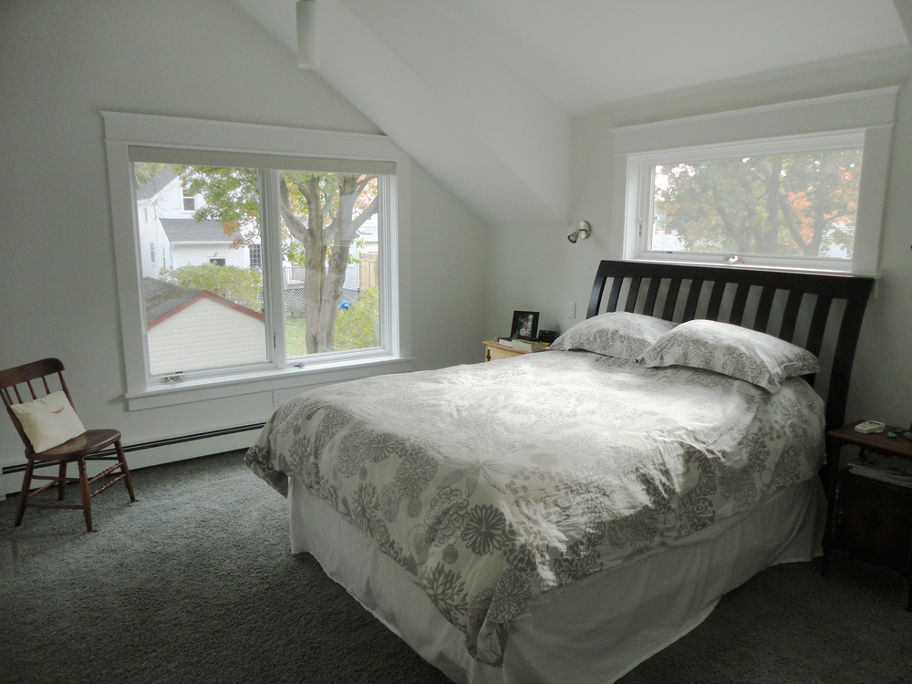 Large windows to the yard and a dormer over the bed give the main bedroom a lofty feel.