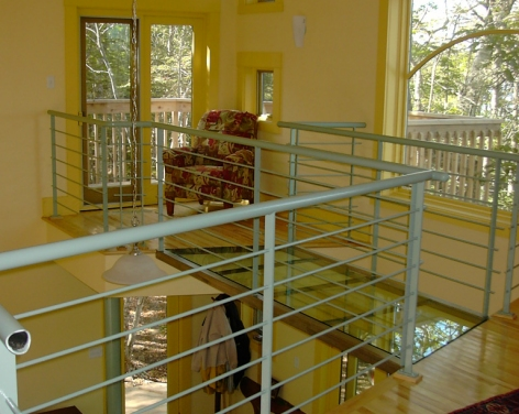 A glass bridge spans to the reading loft and upper deck