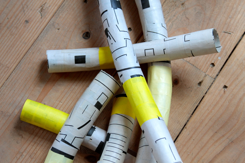 Paper mache newsprint tubes with three shades of yellow origami paper accents.