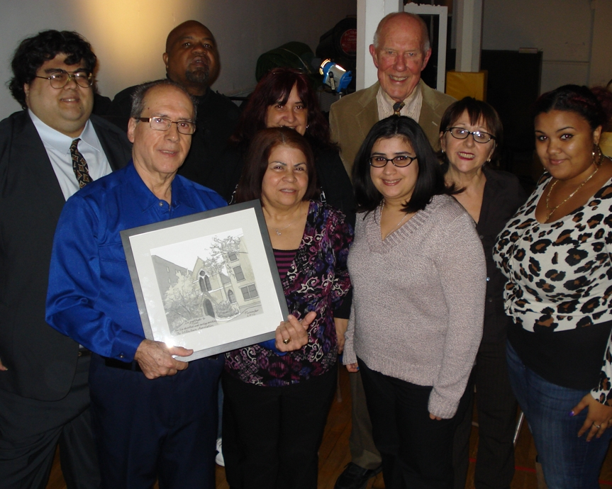 Surrounded by members of his family and Willowtown Association officers, Noel Collado holds his Alfred Award.