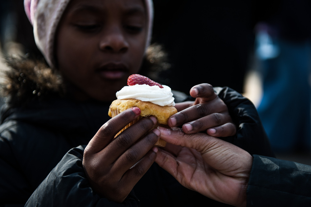 Sherri Mcare hands Talia Mcare a cupcake that they purchased from Stacey Lovelace at the Durham Food Truck Rodeo on Sunday Jan. 27, 2013.