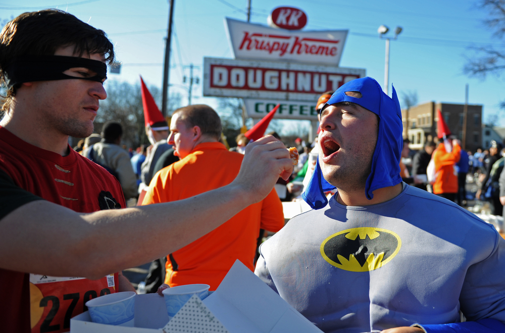 Cullen Domaracki, dressed as Robin, feeds a doughnut to his friend, Jonathan Arcila, dressed as Batman, during the Krispy Kreme Challenge on Saturday, February 9, 2013 in Raleigh, N.C.