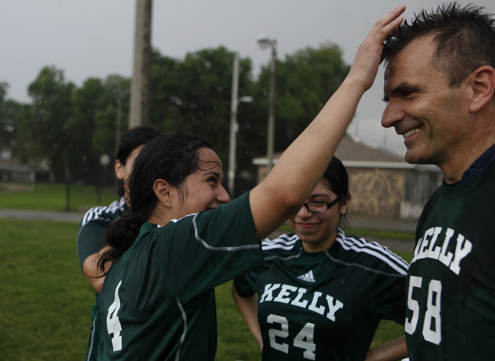 Edith Garcia, a sophomore, spikes Head Coach Stan Mietus' hair after a rainstorm during practice in front of the Kelly High School in Chicago on Tuesday, June 11, 2013.  The Kelly High School girls varsity soccer team is almost entirely first-generation Hispanic Americans.  Many of the girls struggle to convince their parents to allow them to play soccer.