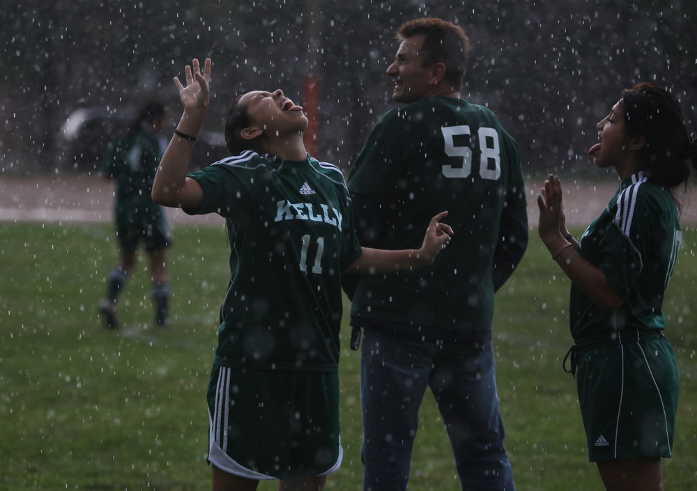 Jennifer Medina, left, and Marbella Rodriquez play in the rain behind their coach, Stan Mietus, during practice in front of the Kelly High School in Chicago on Tuesday, June 11, 2013.  The Kelly High School girls varsity soccer team is almost entirely first-generation Hispanic Americans.  Many of the girls struggle to convince their parents to allow them to play soccer.